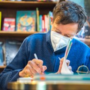 """Wenn die Buchmesse ausfällt: Der Illustrator Philip Waechter signiert eines seiner Bücher in der Frankfurter Buchhandlung """"Tatzelwurm""""."""