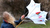 Kampf um die Schirmherrschaft: Eine Frau versucht ihren Regenschirm zu bändigen, doch der Wind scheint stärker.