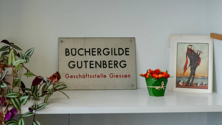 Stillleben: Das historische Schild der Büchergilde Gutenberg in Gießen nebst Bild und Blumen auf einem Regalbrett im Laden an der Wetzsteinstraße