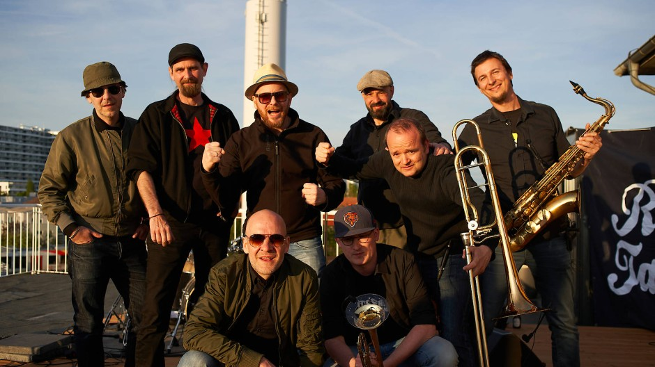 Die Frankfurter Band Revolte Tanzbein posiert mit Saxophon, Posaune und Trompete.