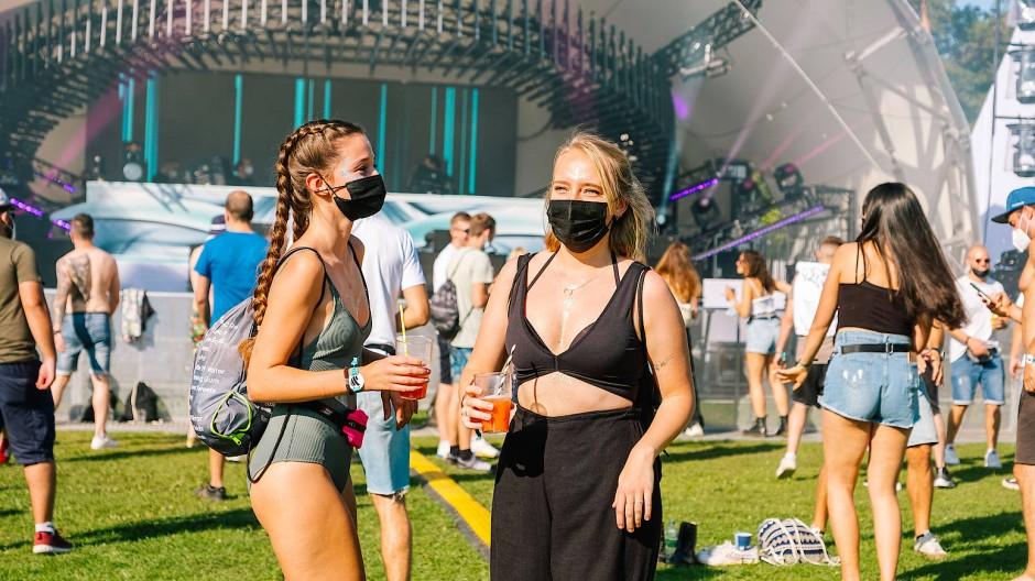 """Party mit Maske in Frankfurt: Tänzer auf der Pool Stage des """"World Club Dome Pool Sessions"""" Techno-Festivals"""