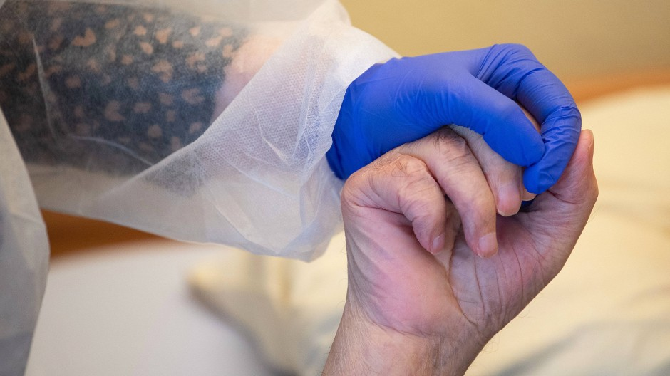 Tuchfühlung: Eine Pflegekraft in Corona-Schutzkleidung hält dem Bewohner eines Altenheims die Hand