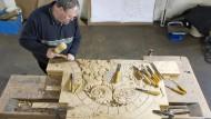 Lippische Handarbeit: Holzbildbauer Wolfgang Koch (oben) bearbeitet Verzierungen für die goldenen Waage.