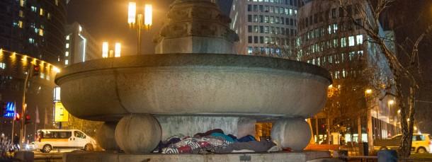 Königliche Schlafstätte: Ein Mann schläft unter dem Merkur-Brunnen an der Messe.