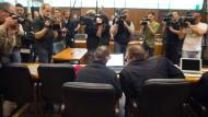 Kurz vor Prozessbeginn Mitte August: Der Angeklagte Abdelkarim E. (links) sitzt neben seinem Anwalt im Saal des Oberlandesgerichts Frankfurt, umringt von Kameraleuten.
