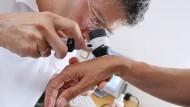 Ein Hautarzt untersucht eine Patientin