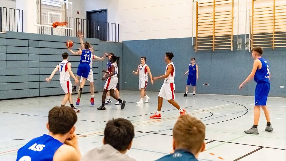 Basketball: Schüler der Carl-von-Weinberg-Schule treten gegen das in blauen Trikots spielende Team der Albert-Schweizer-Schule aus Kassel an.