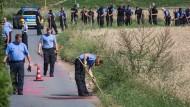 Spurensuche: Polizisten durchkämmen ein Kornfeld in Bischofsheim, wo am Mittwoch einer ihrer Kollegen erschossen wurde.