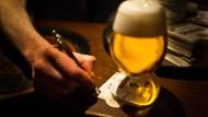 Goldgelbes Leuchten in schummriger Umgebung: Ein Glas Bier wird in einem Frankfurter Lokal serviert.