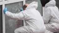 Spurensicherung: Polizisten untersuchen an der zerstörten Scheibe einer Flüchtlingsunterkunft eine Einschussstelle