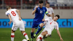 Greece's Katsouranis tries to drive the ball through Switzerland's Inler and Schwegler during their international friendly soccer match in Piraeus
