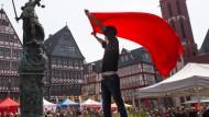Im Zeichen der Gerechtigkeit: Mai-Demonstrant mit roter Fahne unter Gleichgesinnten auf dem Römerberg