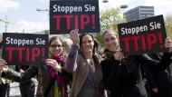 Stoppschilder: Am deutschlandweiten Aktionstag demonstrieren TTIP-Gegner vielerorts, auch in Hessen. Diese drei Frauen stehen auf der Demo in Stuttgart.