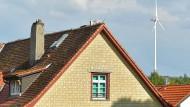 Kontrast: Hinter einem alten Bauernhaus im südhessischen Siedelsbrunn dreht sich ein 200 Meter hohes Windrad.