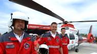 "Die Grundbesatzung: Pilot Swen Silber (links), Notarzt Christian Müller und Assistent Heiko Wagener (rechts) vor dem Hubschrauber ""Christoph Giessen""."