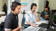"""Tonangebend: Der Syrer Yanal Jarkas (links) und der Kurde Diako Nahid (Mitte) moderieren im Frankfurter Studierendenhaus die Radiosendung """"Good Morning Deutschland""""."""