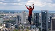 Der Österreicher Reini Kleindl balanciert auf einem 2,5 Zentimeter breiten Band, der so genannten Slackline, über der Frankfurter Skyline. In 185 Metern Höhe bewegt sich der Extremsportler und Kletterer dennoch sicher. Dieser Weltrekord ist Teil des Wolkenkratzer-Festivals.