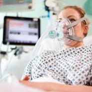 Eine freiwillige Patientin an einer CPAP-Atemhilfe in England.