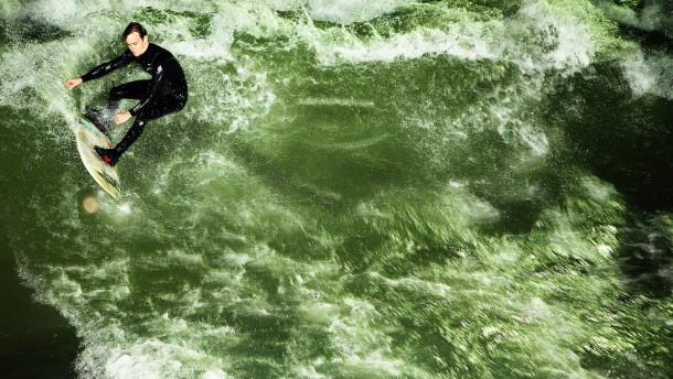 Eisbachsurfen - Unter Flutlicht surfen die Sportler am Eisbach im Englischen Garten in München auf der berühmten Surferwelle.