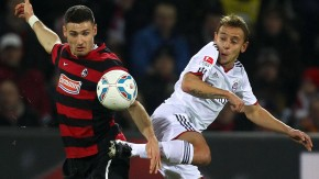 Bayern Munich's Rafinha  is challenged by SC Freiburg's Caligiuri during their German Bundesliga first division soccer match in Freiburg