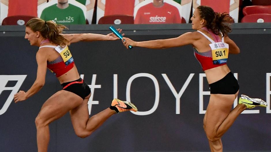 Kontaktsport Leichtathletik: Die echten Sprinterinnen Riccarda Dietsche (rechts) und Ajla Del Ponte aus der Schweiz übergeben de Staffelstab vor Pappkameraden.