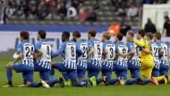 Die Spieler von Hertha BSC setzen kniend ein Zeichen gegen Rassismus.