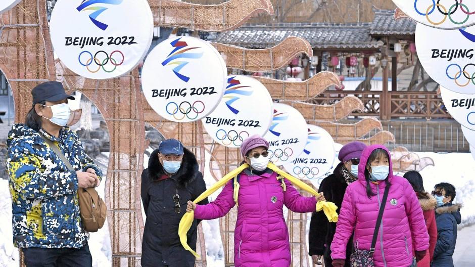 Besucher vor dem Logo der Winterspiele.
