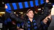In Schwarz und Blau: Lukas Podolski wird bei seiner Ankunft am Mailänder Flughafen am Freitag von Fans gefeiert