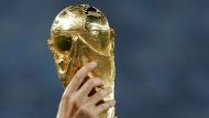 Immer mehr Hände greifen nach dem goldenen WM-Pokal.