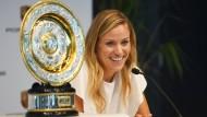 Die Wimbledonsiegerin Angelique Kerber strahlt vor Freude neben ihrer Trophäe bei einer Pressekonferenz.