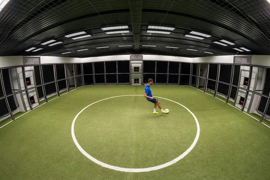 Footbonaut: Der Spieler in der Mitte des Feldes erhält ein Signal, nimmt den Ball an und muss ihn in ein erleuchtetes Zielfeld spielen.
