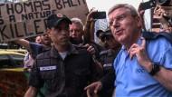 IOC-Präsident Thomas Bach wird von Demonstranten umringt.