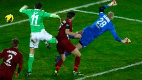 Ivica Olic of Germany's first division Bundesliga club VfL Wolfsburg scores his team's first goal against goalkeeper Robert Wulnikowski of third division club Kickers Offenbach during their German soccer cup, DFB Pokal, quarter final match in Offen