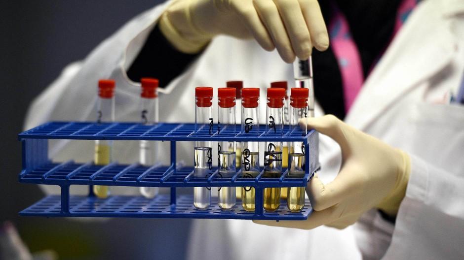 Ein Mitarbeiter der französischen Anti-Doping-Agentur hält Urinproben in einem Träger.