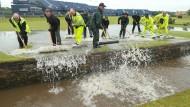 Wasser marsch! Helfer müssen das Grün am Freitag von unzähligen Litern Regenwassern befreien