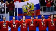 """Vor der russischen Flagge auf den Zuschauerrängen: Die Eishockeymannschaft der """"Olympischen Athleten aus Russland""""."""