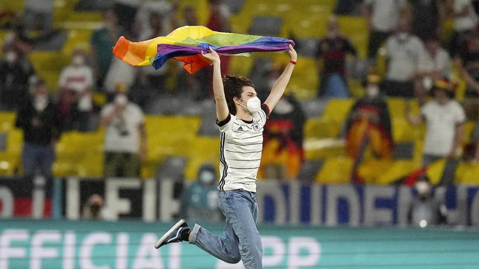 Das Regenbogenthema auf den Rasen getragen: Kurz vor Beginn des Spiels stürmt ein Fan auf den Platz