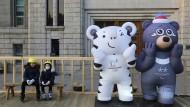 Die Glücksbringer sind bereit: Zwei Kinder sitzen neben den Maskottchen der diesjährigen Olympischen Spiele in der südkoreanischen Stadt Pyeongchang.