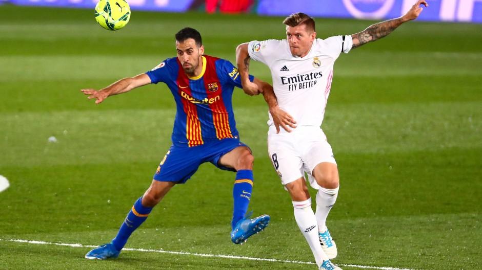 Zweikampf zwischen Madrids Toni Kroos (rechts) und Barca-Spieler Sergio Busquets