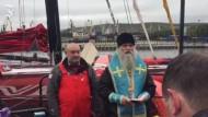 Priester segnet die Segel-Crew