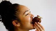 Sieht sogar aus, als würde es schmecken: Diese Dame kostet einen Cupcake, der aus Mehlwürmern gemacht und mit einer Heuschrecke garniert ist.