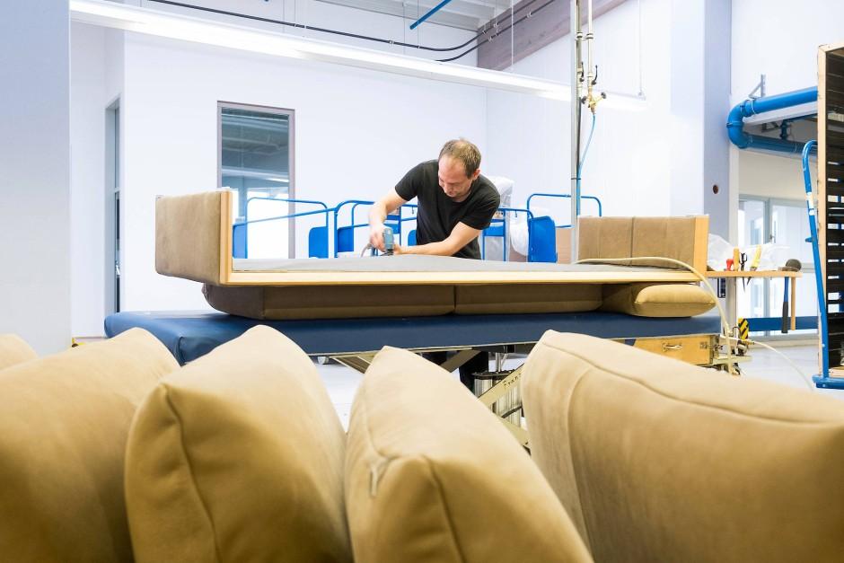 Bei Möbelhersteller Koinor montiert ein Handwerker ein Sofa.