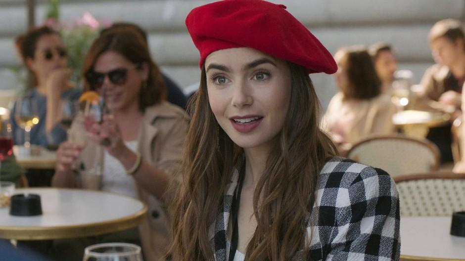 Klischee im Café: Emily mit Baskenmütze und Karo-Blazer. Der Look erinnert auch an die Entwürfe einer wichtigen Designerin in Paris.