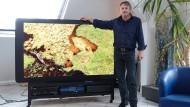 Erfinder Oliver Heine vor einem Großbild-Fernseher