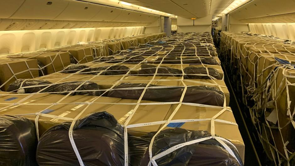 Die in der Passagierkabine festgezurrten Hilfsgüter werden von den Mitarbeitern der Bodendienste Karton für Karton ausgeladen.