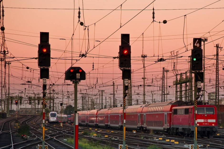 Unter Strom: Verschiedene Lichtsignale und das Kettenwerk der Oberleitung in einem Bahnhofsvorfeld.