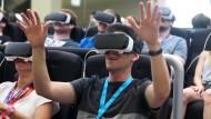 Ein Fachbesucher macht mit einer Virtual-Reality-Brille eine vierdimensionale Achterbahnfahrt.