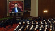 Chinese President Xi Jinping (L) is shown on a screen as he attends the opening session of the Chinese People's Political Consultative Conference (CPPCC) at the Great Hall of the People in Beijing on March 3, 2016.