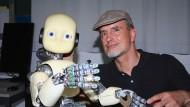 """Der Robotik-Forscher Jürgen Schmidhuber mit einem seiner """"kleinen Roboter"""""""