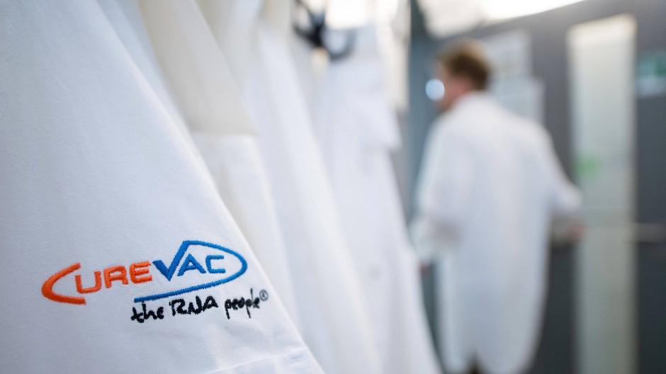 Ein Mann geht hinter einem Labormantel mit dem Logo des biopharmazeutischen Unternehmens CureVac vorbei.